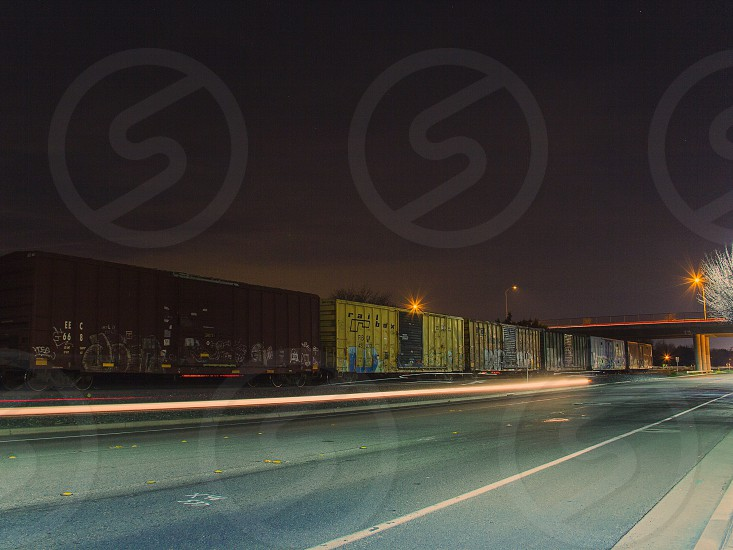 white light trails on road beside brown and green cargo container photo