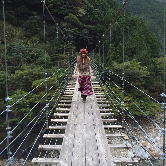 woman in red beanie walking on wooden hung bridge photo