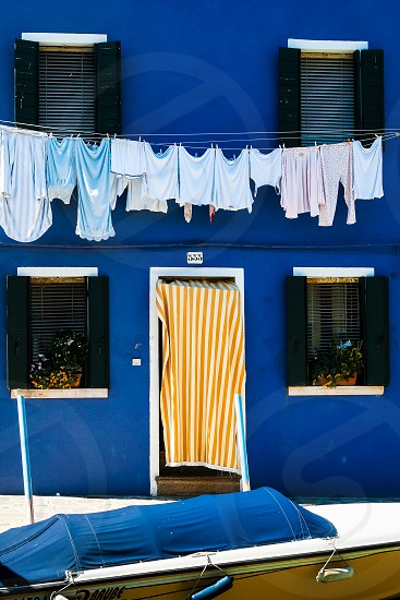 Washing hanging out to dry in front of bright blue building on the island of Burano Venice photo