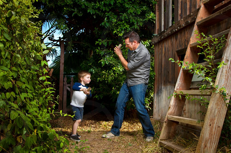 "A father and his son play with pretend ""swords"" that are really toilet paper rolls. photo"