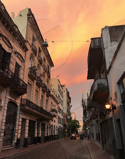 City street old architecture cobblestone pink sunset houses row yellow dramatic san telmo buenos  aires argentina pastel  photo