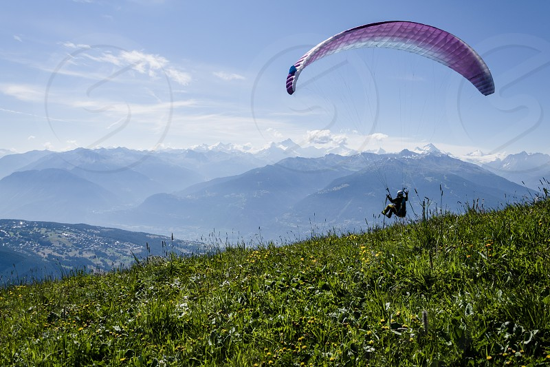 A paraglider starting his flight in the Alps. photo