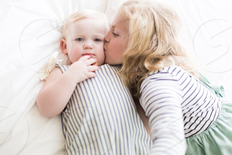 girl kissing infant on cheeks laying on bed photo