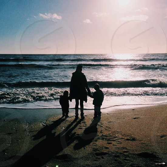 woman and two children silhouette on seashore  photo