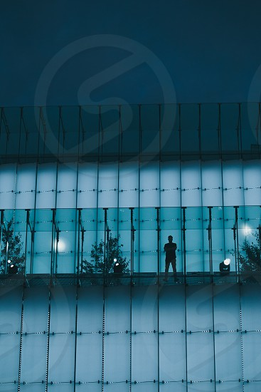 Silhouette of man standing on backlit glass construction in a city center at night photo