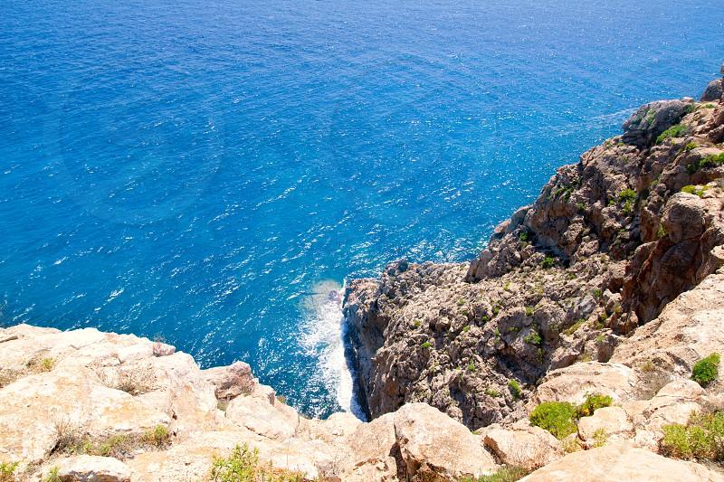 Mediterranean sea foam rocky shore in formentera Barbaria cape photo