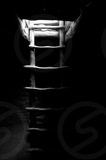grayscale photo of wooden ladder leading to well lit area from dark room photo