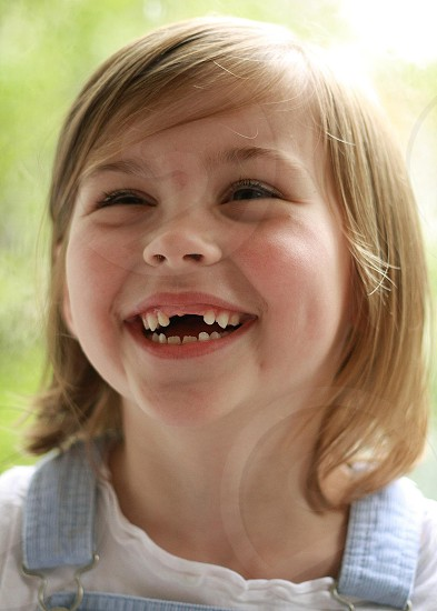 A young girl with two missing front teeth laughs. photo