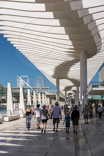 People Walking under the Modern Pergola in the Harbour Area of Malaga photo