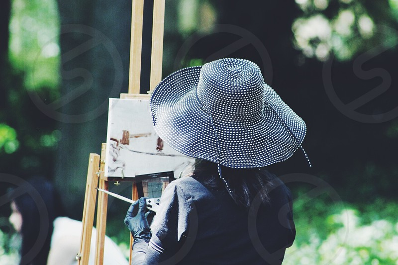 back of a woman wearing a blue white woven floppy hat painting at an easel with trees in the distance photo