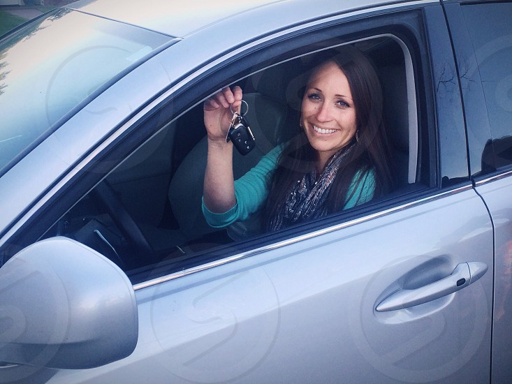 Brunette woman in car confidently holding keys photo