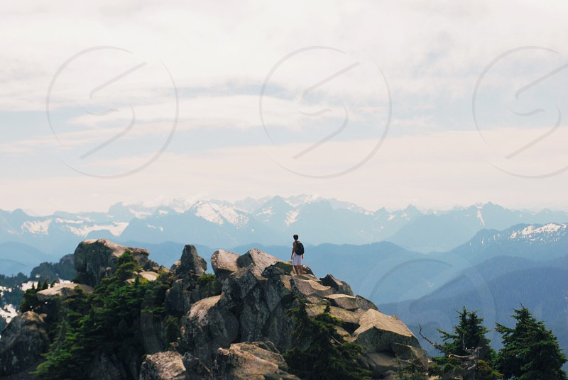 person walking on brown rock mountain photo