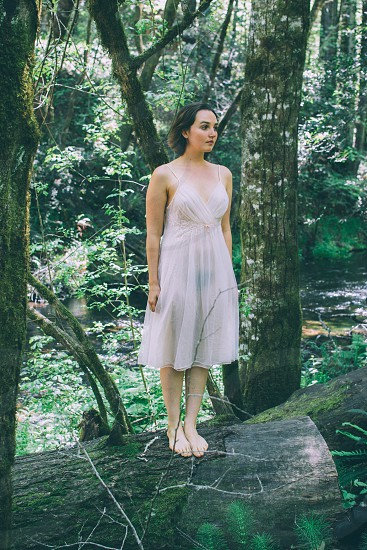 woman in white baby doll dress standing on tree trunk photo
