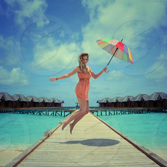 woman in orange dress holding umbrella while doing jump shot in beige wooden pathway near body of water during daytime photo