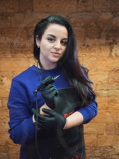 Portrait of beautiful brunette girl with tattoo machine looking at the camera. Artist in leather apron and black sterile gloves posing with gun. photo