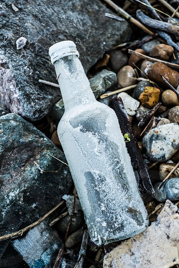 Frosted old empty bottle on the ground portrait format stones grass  photo
