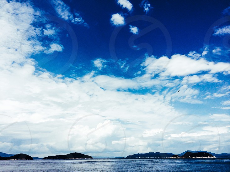blue body of water under white clouds and blue sky photo