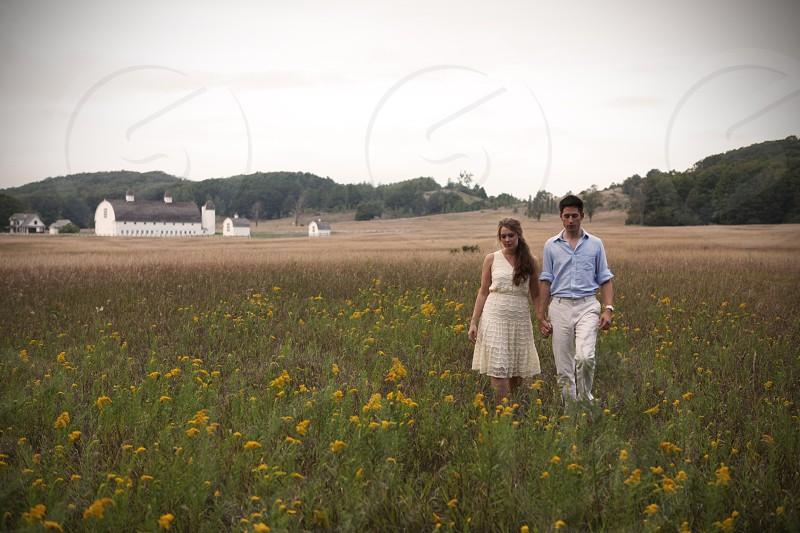 couple walking on yellow flower field photo