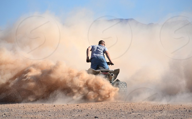 Man riding four wheeler kicking up dust clouds photo