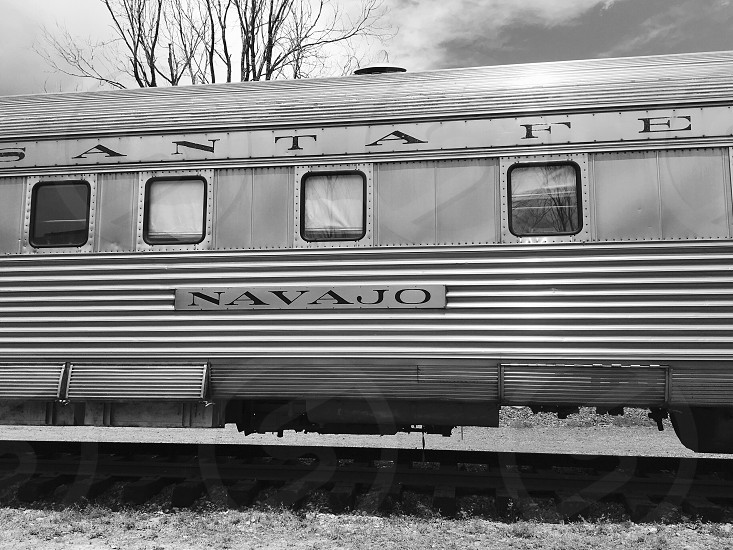 greyscale photography of navajo train traveling under cloudy sky during daytime photo