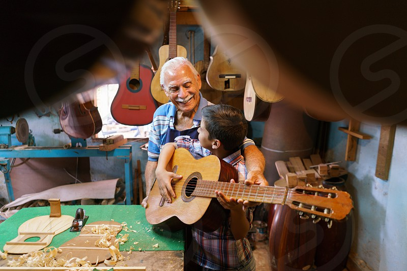 music; grandpa; teaching; grandson; boy; playing; guitar; acoustic; active; artisan; child; class; classic; classical guitar; crafts; elderly; family; fun; gap; generations; grandchild; grandfather; happy; hispanic; instrument; job; kid; learn; learning; lesiure; lesson; lifestyle; luter; lutist; maker; man; old; passion; people; retired; retirement; senior; shop; smiling; teacher; together; work; working; workshop photo