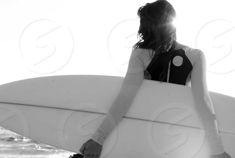 Woman young woman surfer surfboard sunlight lens flare black and white wetsuit beach ocean long hair Pacific Ocean Southern California photo