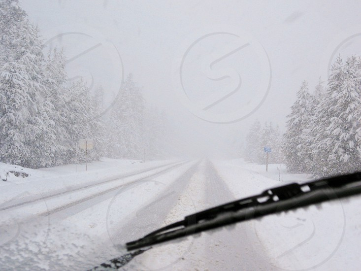 Dangerous driving conditions during blizzard on rural highway seen through car windshield. photo