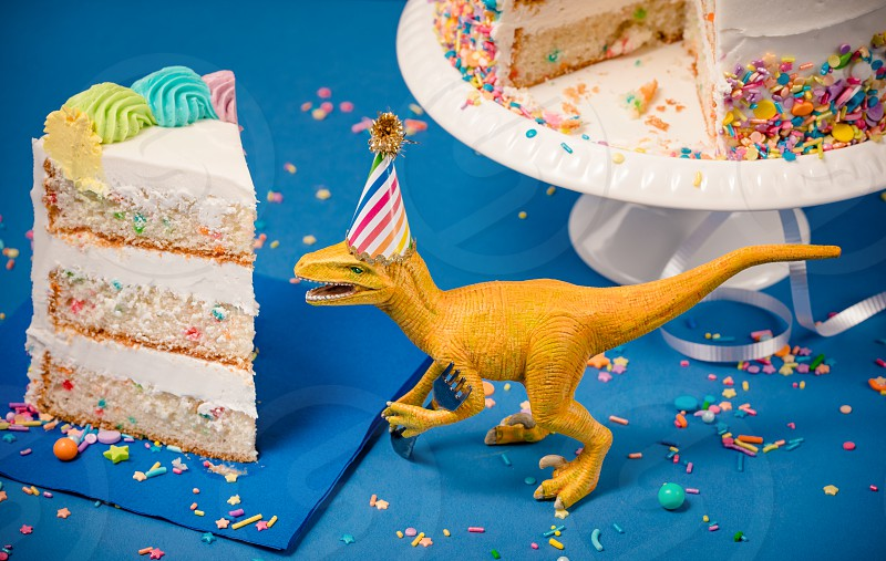 Toy Dinosaur wearing a party hat next to a slice of birthday cake photo