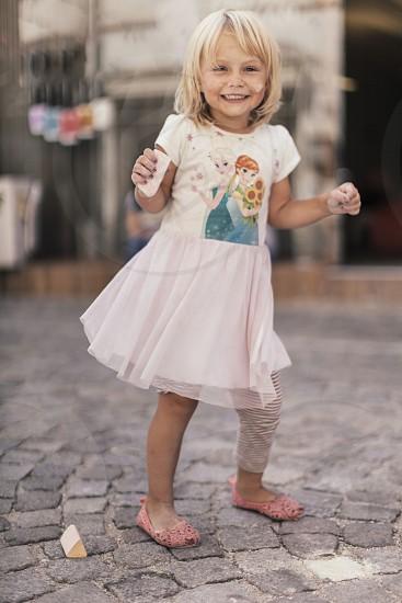 girl in disney frozen crew neck short sleeve mini dress standing on concrete tiles floor at daytime photo