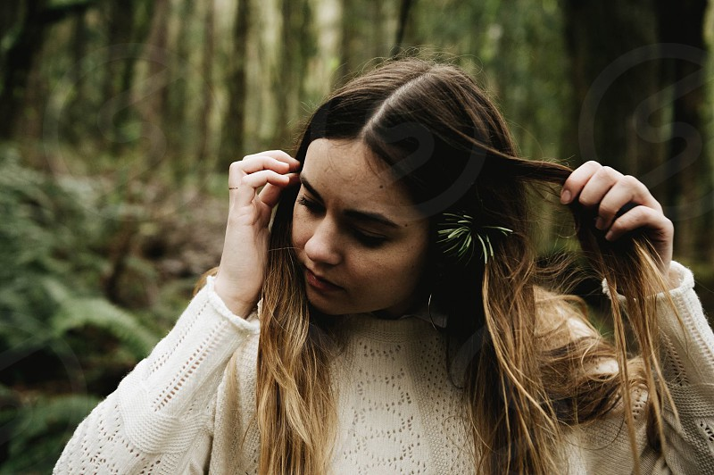 woman with long brown hair and white sweater in woods photo