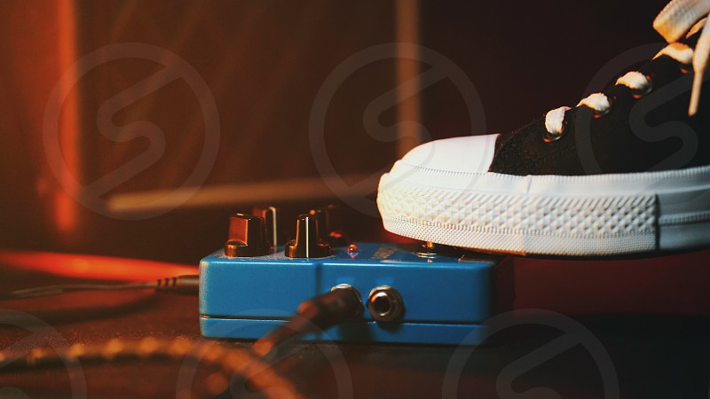 Close up of guitar player foot pressing pedal. Musician uses music effect loop machine. Man in trendy sneakers his foot playing at stage during concert. Macro view. photo