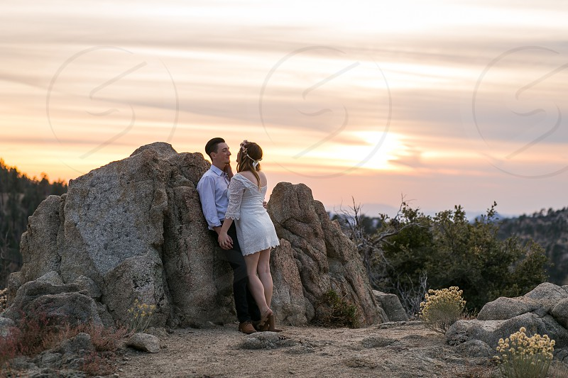 man in white dress shirt standing against brown rock in front of woman in white dress holding hands during sunset photo