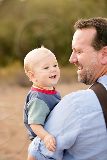 smiling man carrying smiling toddler photo