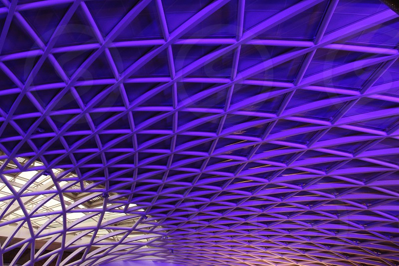 Purple lighting on the triangular roof structure of Kings Cross station London photo
