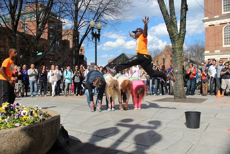 people bent over touching toes in plaza with crowd photo