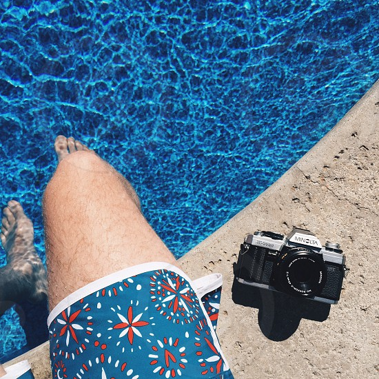 person in blue orange and white shorts sitting on swimming pool ledge with camera beside him photo