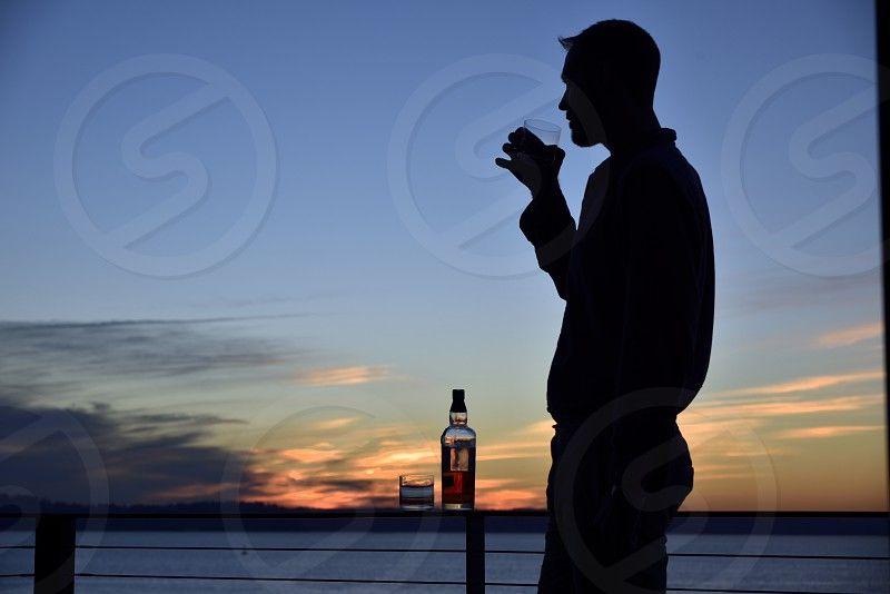 Happy hour sunset drinks whiskey scotch drinking silhouette man handsome photo