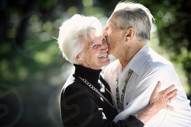 Bathed in sunlight an elderly man kisses his elderly wife / girlfriend on her cheek as she laughs and hugs him in a natural outdoor setting. photo