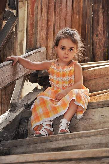 girl in yellow orange and white floral printed sleeveless dress sitting on wooden stairs photo