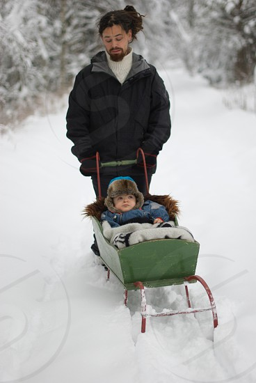 man pushing child in sled on snow covered ground photo