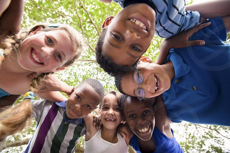 smiling; hug; hugging; child; children; circle; 8-9; african; around; black; boys; camera; carefree; caucasian; cheerful; elementary age; embrace; embracing; emotions; enjoy; female; friend; friendship; fun; future; girl; girls; group; happy; hispanic; joy; kids; laughing; leisure; looking; low angle; nature; optimism; outdoors; park; people; persons; playing; positive; recreation; students; team; tree; together; young photo