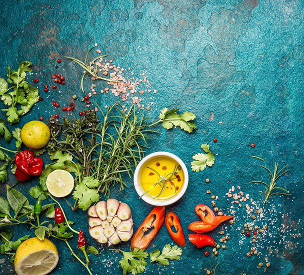Fresh herbs and spices on blue turquoise background. - garlic laurel lime rosemary parsley pepper. photo