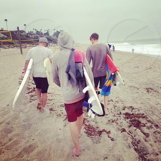 3 men holding white surfboard on the seashore photo