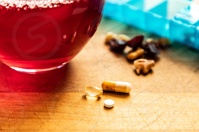 Morning pills  nuts and cranberries with juice to wash them down photo