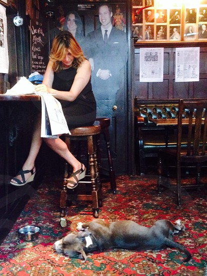 woman in black sleeveless dress sitting on bar stool looking down on black dog lying on the floor photo