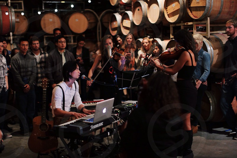 man sitting at a table with a keyboard laptop and microphone performing for a crowd in a wine cellar photo