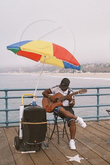 man playing the brown acoustic guitar photo