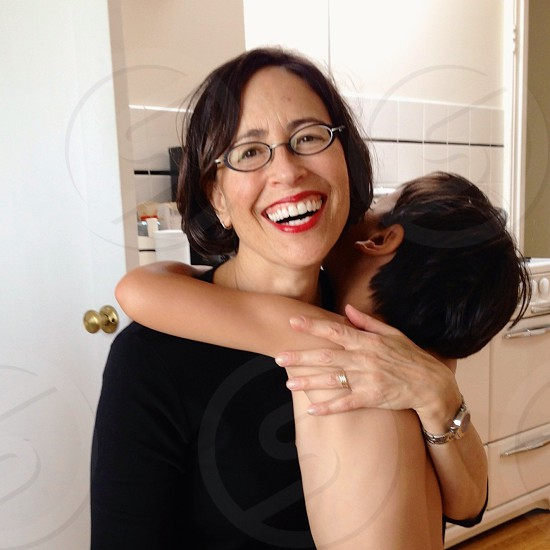 son hugging mother at the kitchen photo