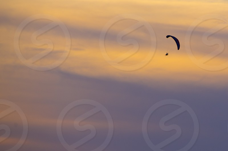 silhouette of person with open parachute in sky during golden hour photo