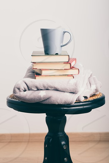 A few books with cup of coffee and blanket on wooden chair photo